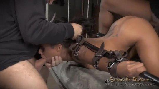 Два типа разъебывают прикованную рабыню негритянку в рот и вагину