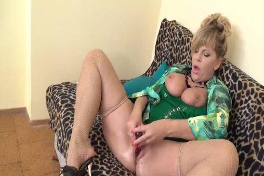 Зрелая блондинка с большими сиськами мастурбирует на диване