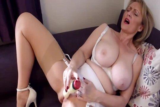 Зрелая блондинка с большой натуральной грудью мастурбирует вибратором на диване