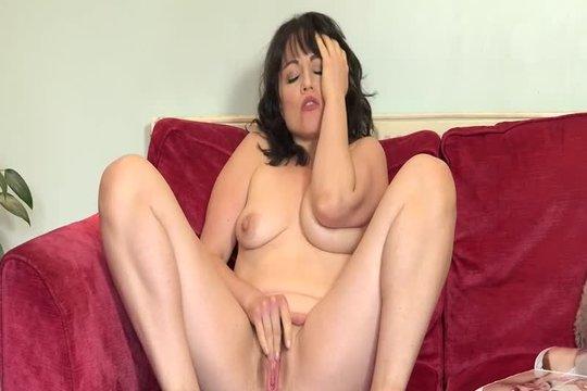 Зрелая брюнетка мастурбирует на диване, представляя молодой член